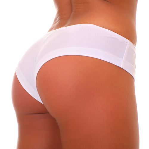 Tan girl's behind from the waist down in white underwear on a white background