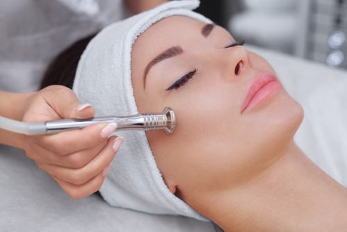 cosmetologist makes the procedure microdermabrasion of the facial skin of a beautiful, young woman in a beauty salon-img-blog