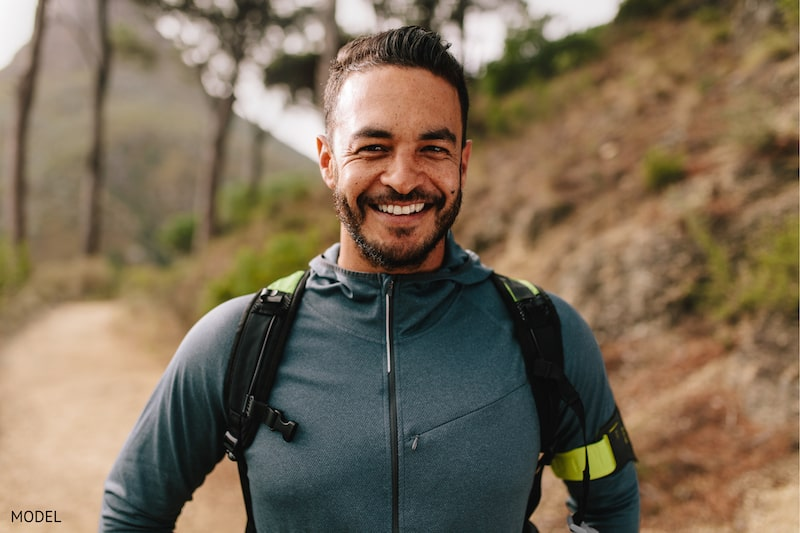 Happy man with a backpack smiling on a hike.