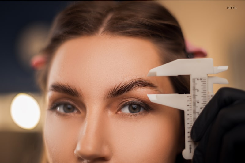 Woman getting her eyebrow measured by someone with a gloved hand.